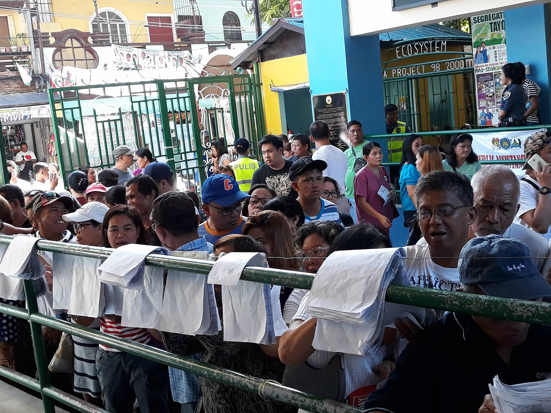Voters look up their assigned precincts in Las Piñas East National High School. Photo by Karol Ilagan